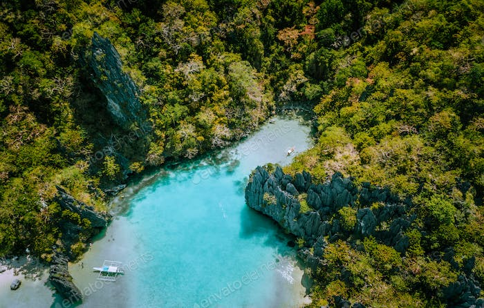 Aerial drone view of blue turquoise transparent lagoon water of tropical island with rugged steep