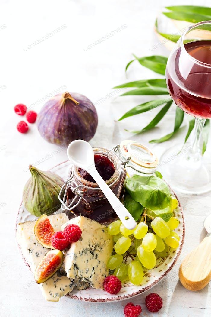 Sortiment von Käse, Beeren und Trauben mit Rotwein in Gläsern auf Stein Hintergrund. Kopierbereich