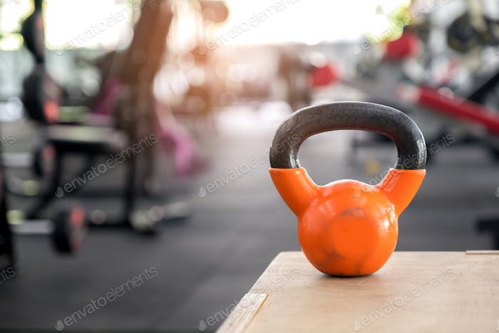Orange kettlebell put on a wooden crate.