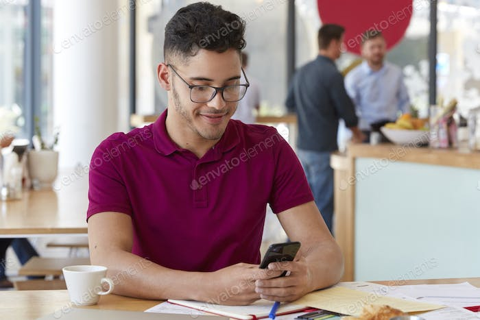 People, career, technology concept. Handsome male hipster in spectacles holds cellular, enjoys onlin