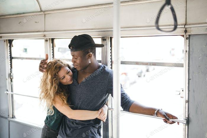 многоэтническая пара, путешествующая на трамвае