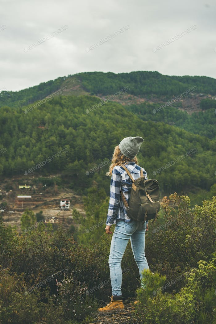 Young woman traveler hiking in the mountains, rear view