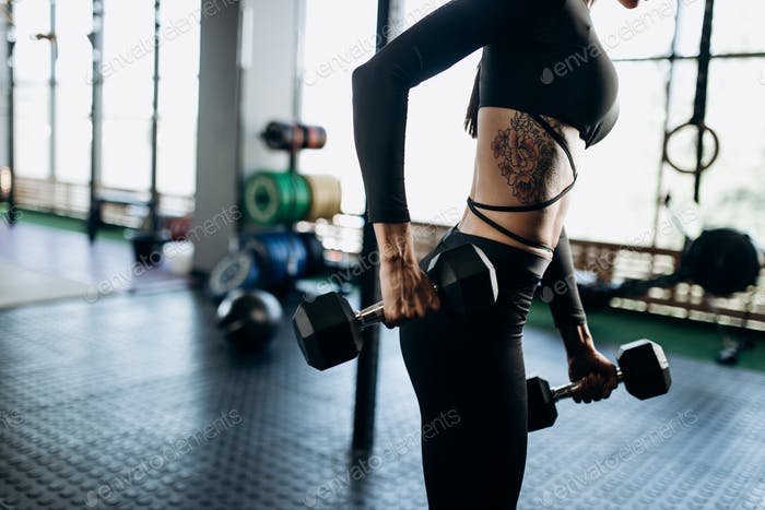 Slender body of a young woman with tattoo in a black sportswear that is doing exercises with