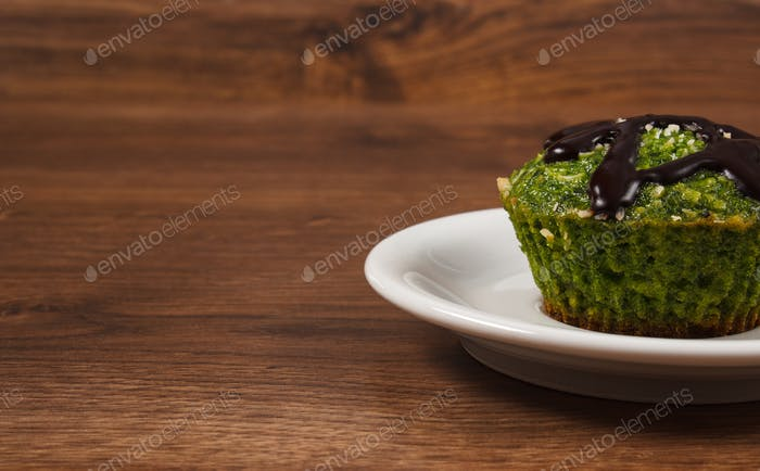 Fresh muffin with spinach, desiccated coconut and chocolate glaze