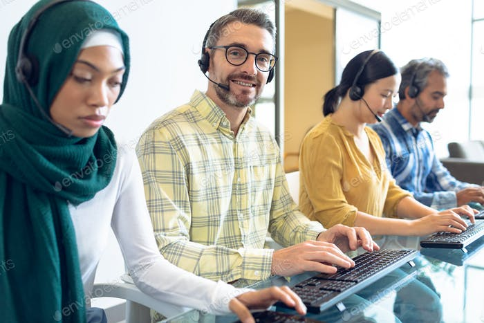 Side view of diverse customer service executives talking on headset at desk in office