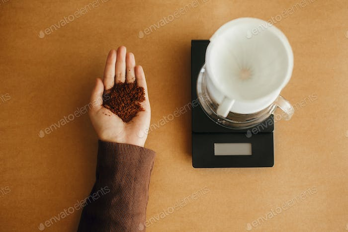 Grind coffee close up in hand