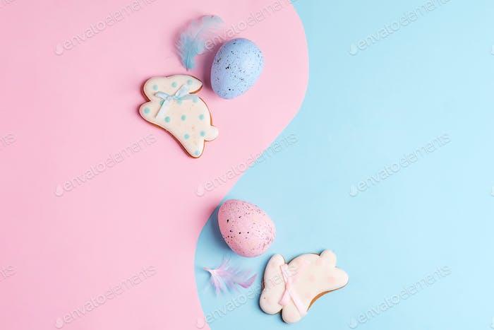 Zwei handgefertigte Ostereier und Kekse auf einem duotone pastellfarbenen Hintergrund als Symbol für