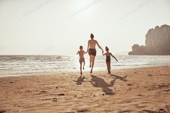 Mother and children holding hands while skipping along a beach