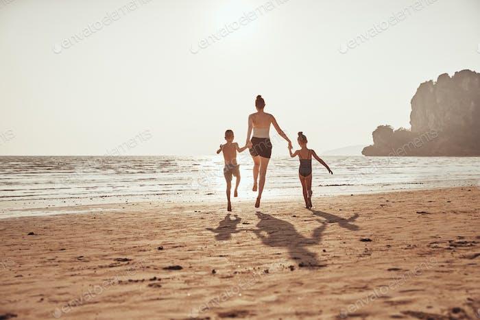 Madre y niños tomados de la mano mientras saltando a lo largo de una playa