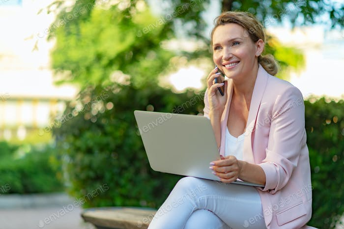 Close-up portrait of a smiling woman calling by phone on the street.