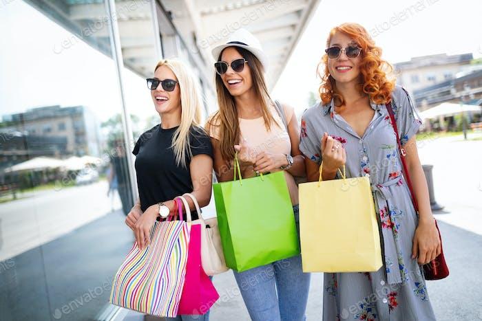 Shopping, fun and tourism concept. Beautiful girls with shopping bags in ctiy