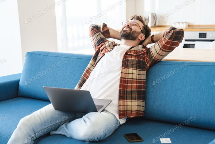 Portrait of young happy man smiling and using laptop on sofa at home