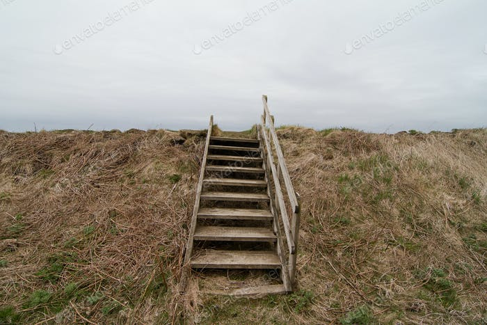 Damaged old wood stairway over a grass hill