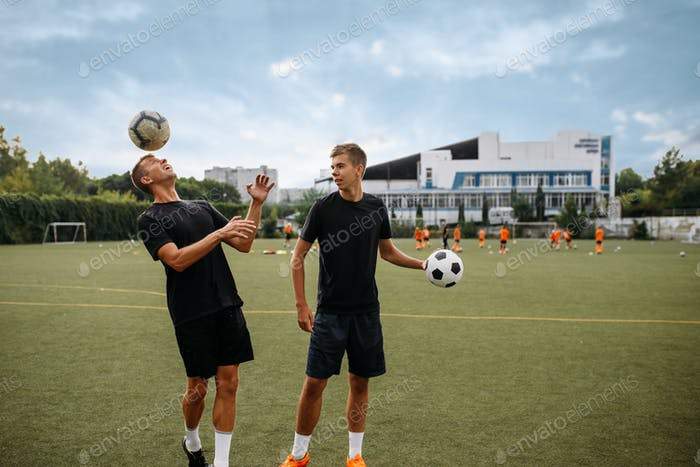 Soccer players training with balls on the field