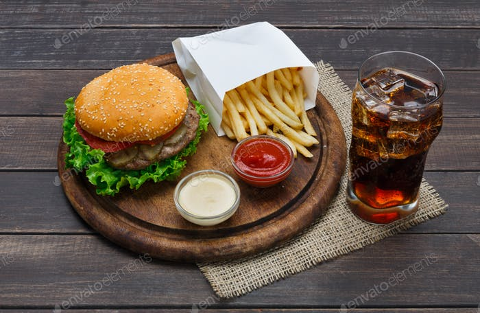 Fast food take away. Hamburger, cola and fries on wood