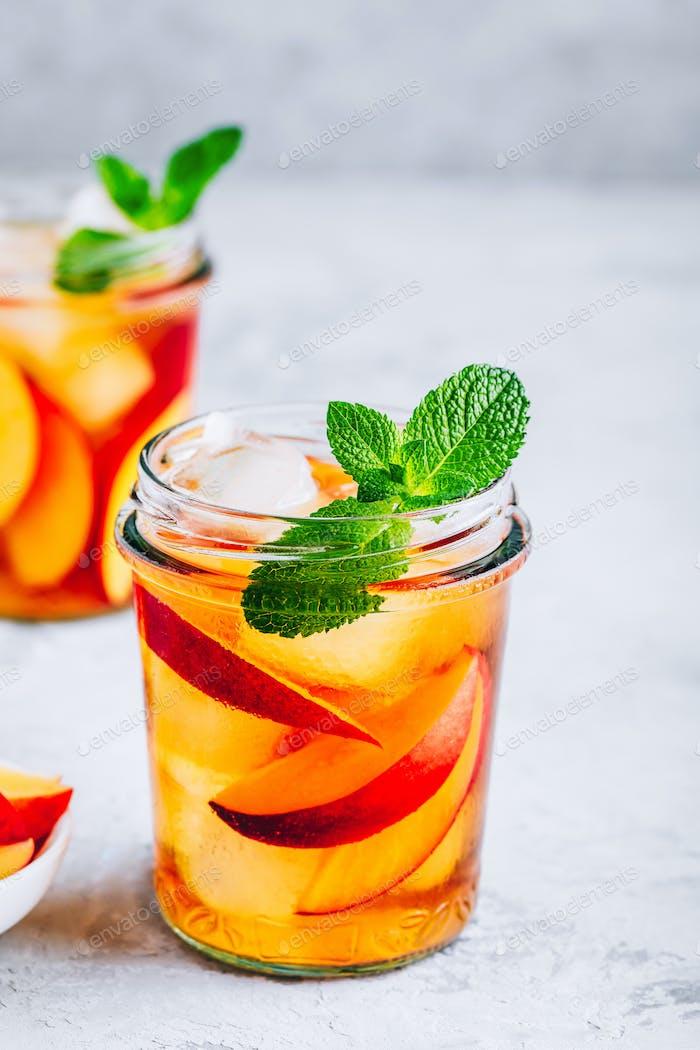 Hausgemachter Pfirsich-Eistee oder Limonade mit frischer Minze und Eiswürfeln im Glas