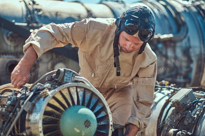Mechanic in uniform repairing the dismantled airplane turbine in an open-air museum.