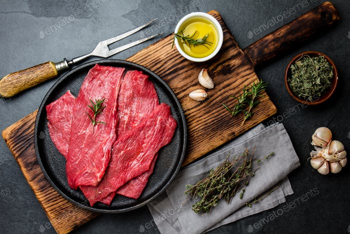 Beef tenderloin in cast iron pan on wooden board, spices, herbs, oil on slate gray background.