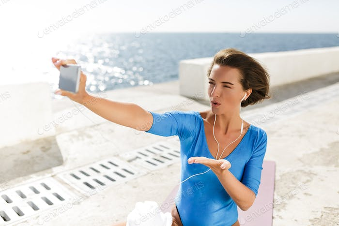 Woman with dark short hair in blue swimsuit sitting on yoga mat and looking in her mobile phone