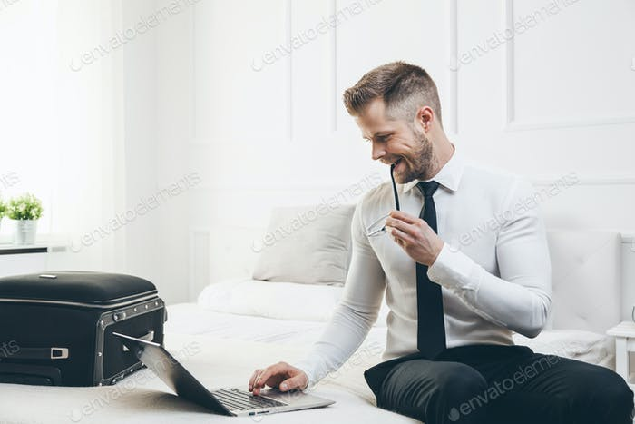 Geschäftsmann auf dem Bett arbeitet mit einem Laptop aus seinem Hotelzimmer
