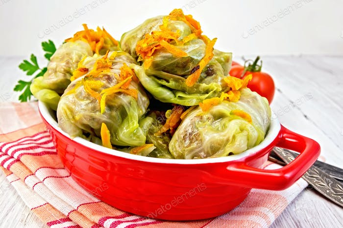Cabbage stuffed and carrots in pan on board