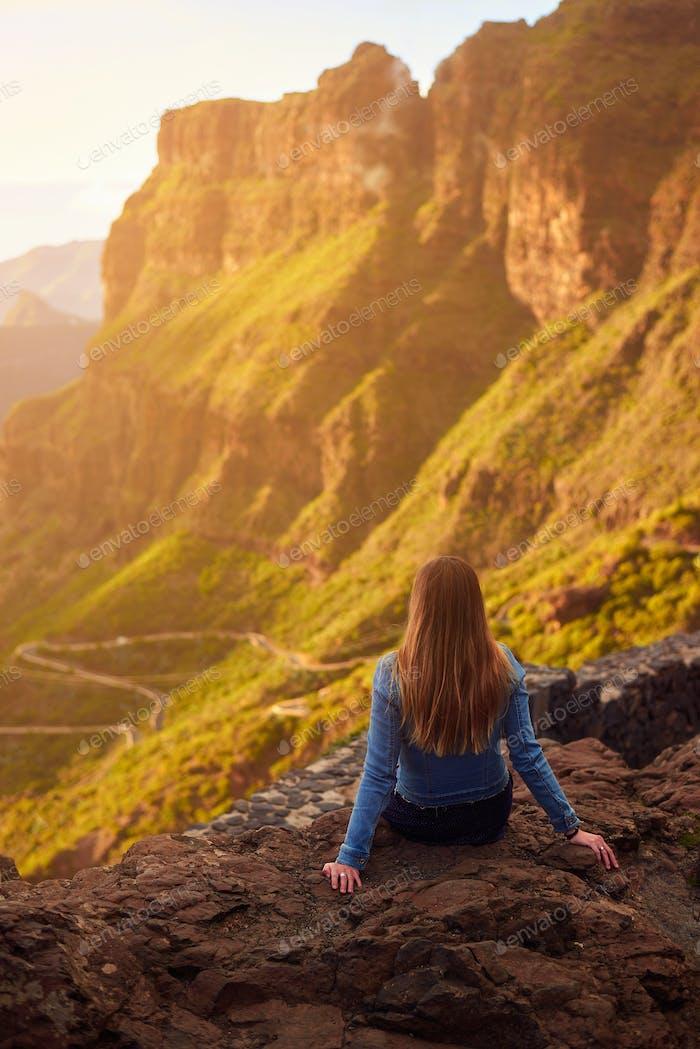 Junge Frau betrachten die Straße nach Masca auf Teneriffa, Kanarische Inseln, Spanien