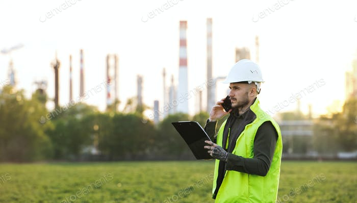 Young engineer with smartphone standing outdoors by oil refinery. Copy space
