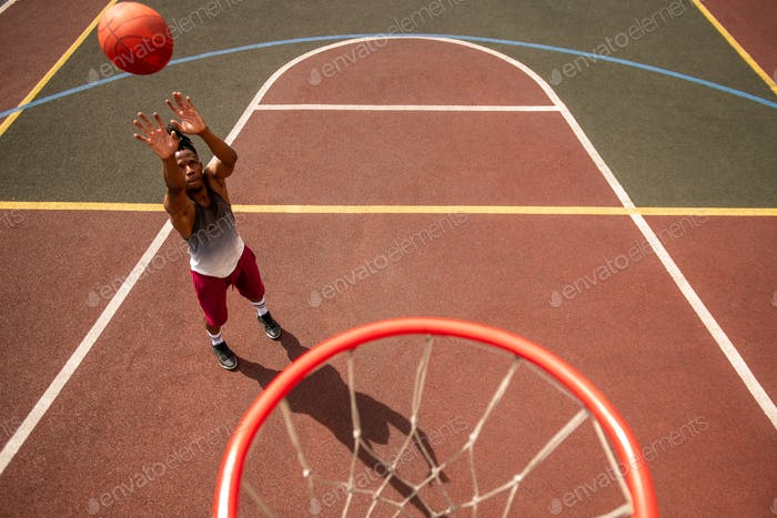 Young professional basketballer in activewear throwing ball in basket