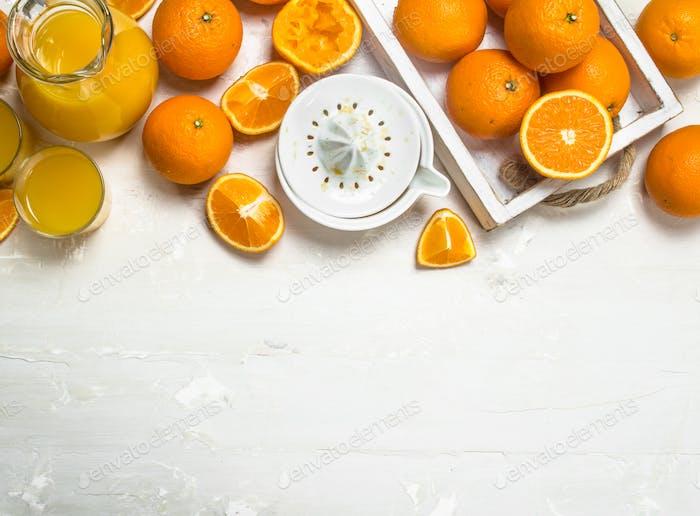 Orange juice in pitcher and juicer.