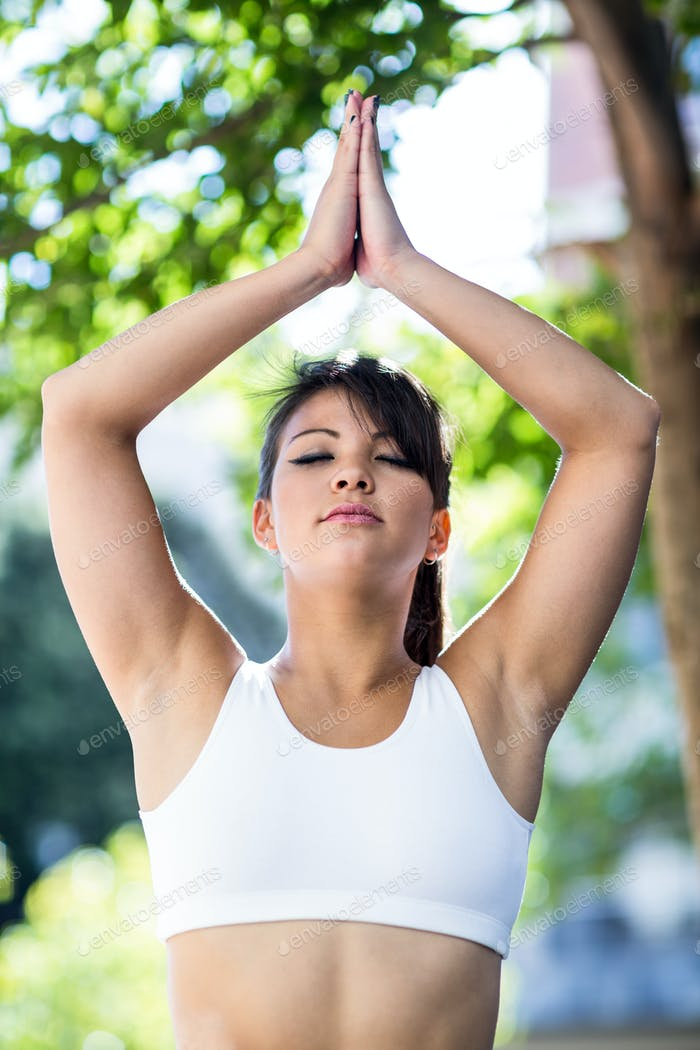 Peaceful athletic woman doing yoga with eyes closed in the city