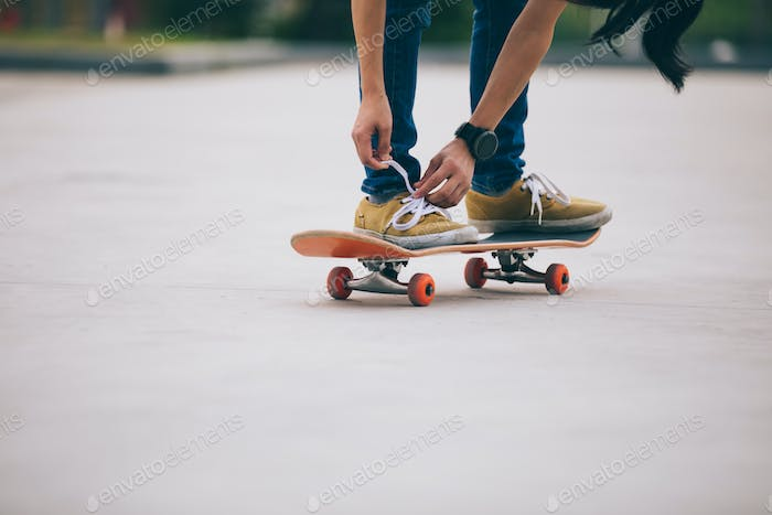 Skateboarder tying shoelace on skateboard