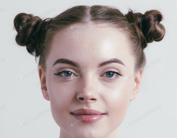 Porträt von brünette Frau mit Brötchen aus dunklem Haar.