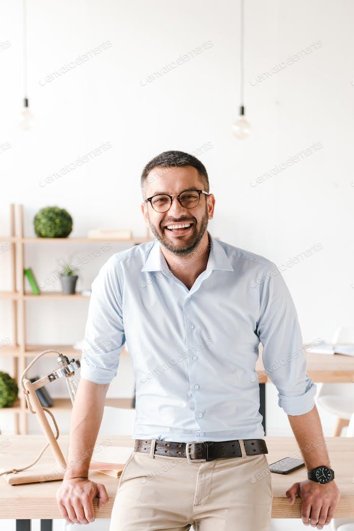 Happy portrait of businesslike man wearing white shirt sitting o