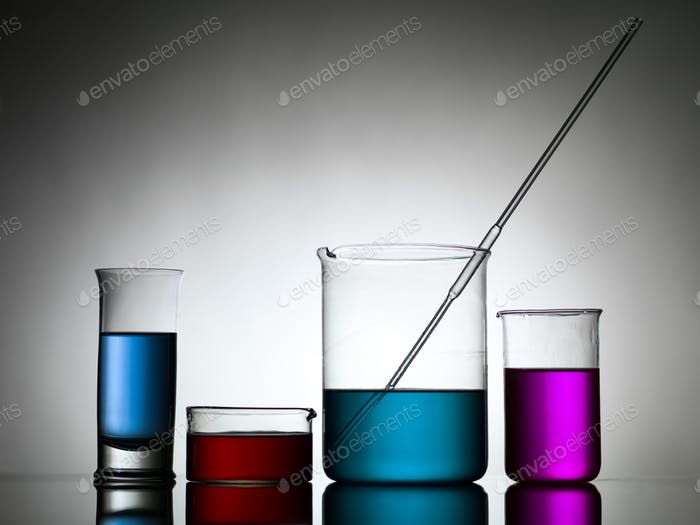 beakers with dropper and colored liquid substances
