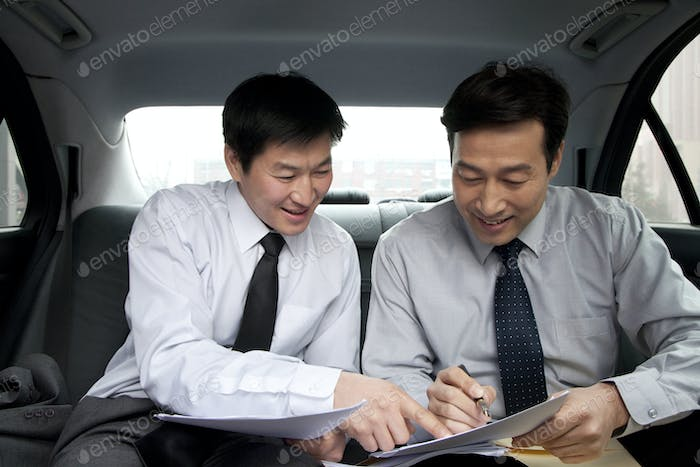 Business people discussing inside of a car