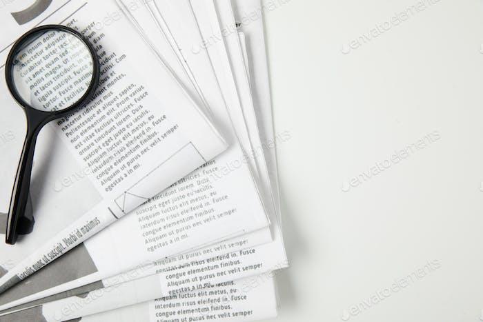 vista superior de lupa y periódicos sobre gris, concepto de información