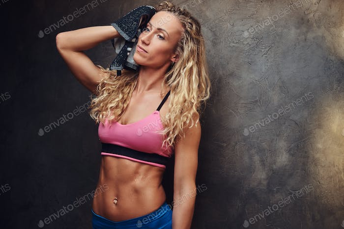 Beautiful blonde fitness woman in training suit after hard workout in gym