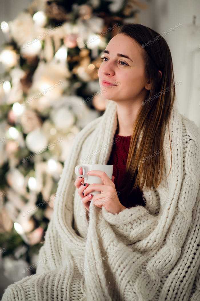Young beautiful woman with sitting home holding cup of hot coffee wearing knitted warm sweater