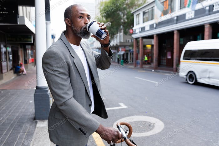 African American businessman holding his bike and a takeaway coffee