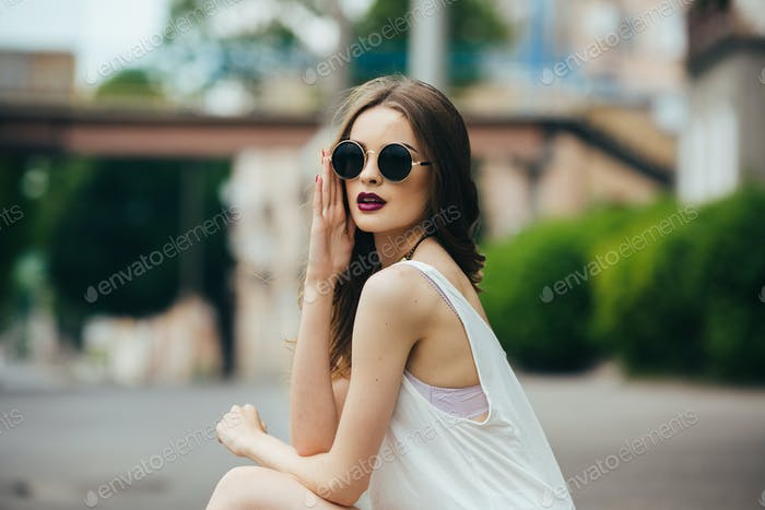 schöne Mädchen in Sonnenbrille sitzen