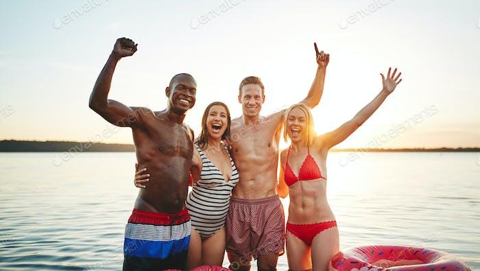 Lächelnde Gruppe von Freunden Spaß in einem See bei Sonnenuntergang