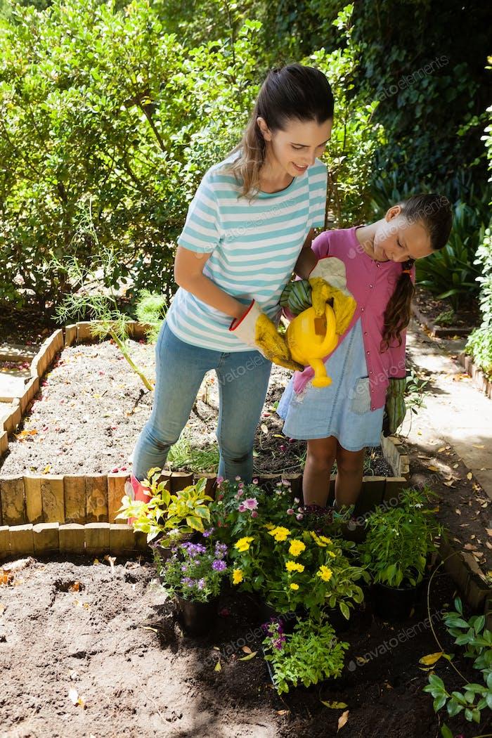 Lächelnde Frau und Tochter gießen Blumen