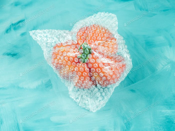 Tomato in plastic package on turquoise