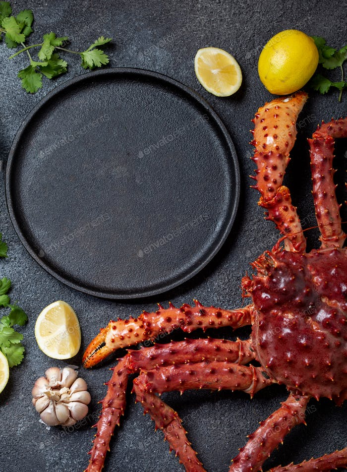 Food background with empty black plate, fresh king crabs