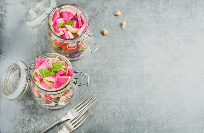 Healthy vegetarian salad in jars over grey concrete background