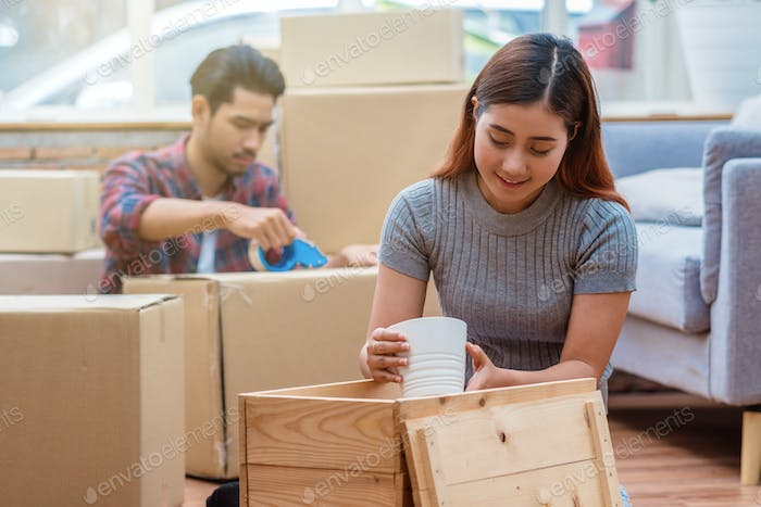 Asian young couple packing the big cardboard box for moving in new house
