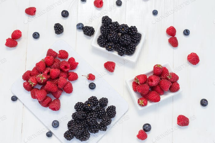 Blueberries, raspberries and blackberries on white background