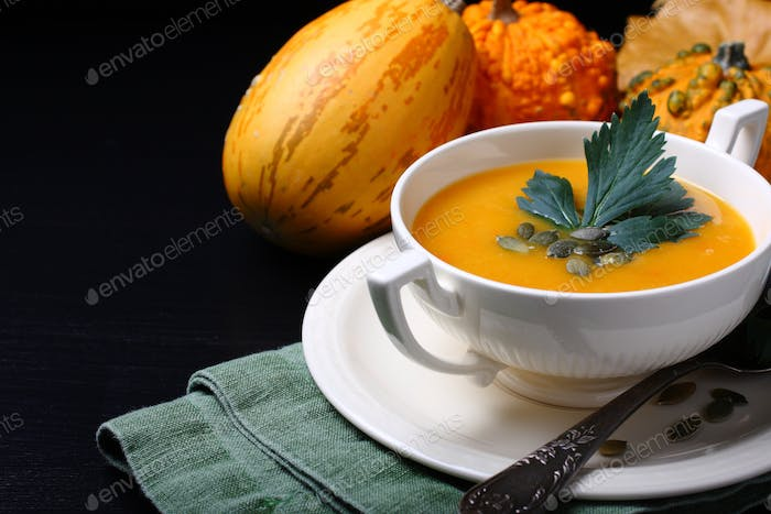 Pumpkin soup in white plate with celery leaves