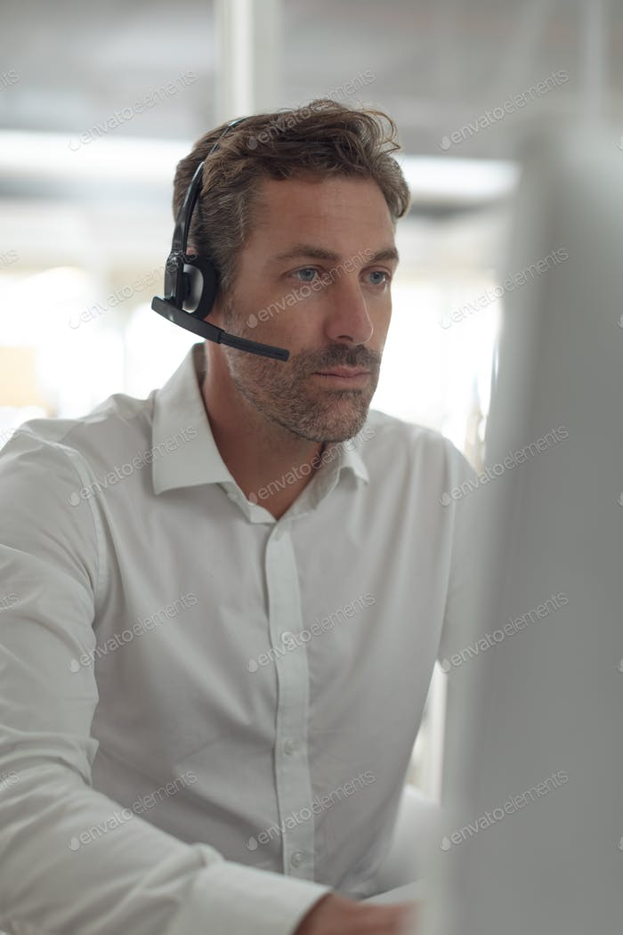 Front view of attentive Caucasian male customer service executive working at desk in a modern office