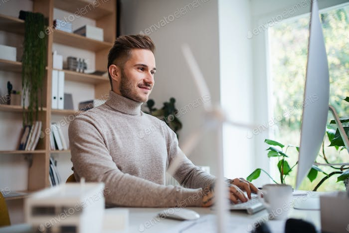 Young businessman sitting at the desk indoors in office, using computer.